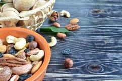 Διαφορετικοί τύποι καρυδιών και σταφίδων χρήσιμα ιχνοστοιχεία καρυδιών ενός στα ξύλινα υποβάθρου στοκ φωτογραφία