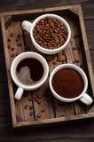 Διαφορετικοί τύποι καφέ - που αλέθονται, σιταριών και ποτών στο σκοτεινό ξύλινο υπόβαθρο στοκ εικόνες με δικαίωμα ελεύθερης χρήσης