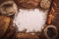 Διαφορετικοί τύποι ψωμιών στον ξύλινο πίνακα που ξεσκονίζεται με το αλεύρι Στοκ Φωτογραφία