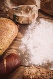 Διαφορετικοί τύποι ψωμιών στον ξύλινο πίνακα που ξεσκονίζεται με το αλεύρι Στοκ Φωτογραφίες