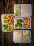 Διαφορετικοί τύποι take-$l*away τροφίμων στα microwavable εμπορευματοκιβώτια σε ένα ξύλινο υπόβαθρο στοκ εικόνες