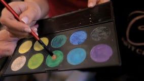 διαφορετικός επαγγελματίας σκιών ματιών καλλυντικών χρωμάτων Ο καλλιτέχνης σύνθεσης επιλέγει τα καλλυντικά για τον πελάτη στο σαλ απόθεμα βίντεο