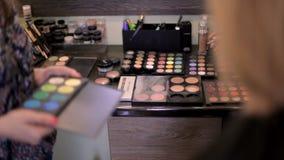 διαφορετικός επαγγελματίας σκιών ματιών καλλυντικών χρωμάτων Ο καλλιτέχνης σύνθεσης επιλέγει τα καλλυντικά για τον πελάτη στο σαλ φιλμ μικρού μήκους