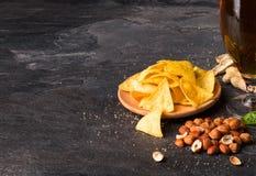 Διαφορετικό άχρηστο φαγητό σε ένα μαύρο υπόβαθρο nachos πικάντικα υγιή καρύδια Μια πίντα της σκοτεινής μπύρας Έννοια φραγμών διάσ στοκ φωτογραφία