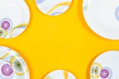 Διαφορετικό πλαίσιο πιάτων μεγεθών, φωτεινό κίτρινο υπόβαθρο, διάστημα αντιγράφων Στοκ Εικόνα