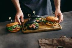 Διαφορετικό ψημένο στη σχάρα burgers κρέας βόειου κρέατος πινάκων εκμετάλλευσης ατόμων Στοκ εικόνα με δικαίωμα ελεύθερης χρήσης