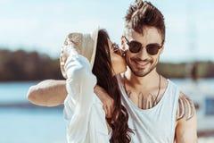 Διαφυλετικό ζεύγος στα γυαλιά ηλίου που αγκαλιάζει ενώ κορίτσι που φιλά το φίλο της Στοκ Εικόνες