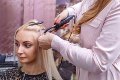 Διαδικασία επεκτάσεων τρίχας Ο κομμωτής κάνει τις επεκτάσεις τρίχας στο νέο κορίτσι, ξανθό σε ένα σαλόνι ομορφιάς Εκλεκτική εστία Στοκ φωτογραφία με δικαίωμα ελεύθερης χρήσης