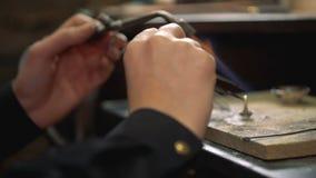 Διαδικασία που ανοπτεί ένα ασημένιο δαχτυλίδι που καταναλώνει έναν συγκολλώντας σίδηρο στο χέρι του κοντά φιλμ μικρού μήκους