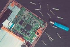 Διαδικασία της επισκευής συσκευών ταμπλετών PC κοντά στο κατσαβίδι και το κομμάτι στο μαύρο ξύλινο υπόβαθρο Τοπ όψη αποσυντεθειμέ Στοκ Φωτογραφίες