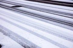 Διαδρομές ελαστικών αυτοκινήτου αυτοκινήτων στο χιονώδη δρόμο Στοκ Φωτογραφία