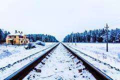 Διαδρομές σιδηροδρόμου στο κίτρινο σπίτι χειμερινού χιονιού Στοκ Εικόνες