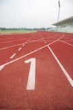 Διαδρομή αριθμός 1 έναρξης στην κόκκινη τρέχοντας διαδρομή Στοκ Εικόνες
