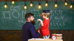 Διδακτική έννοια συνομιλίας Παιδί στο διαβαθμισμένο ακούοντας δάσκαλο ΚΑΠ, πίνακας κιμωλίας στο υπόβαθρο, οπισθοσκόπο δάσκαλος στοκ εικόνες