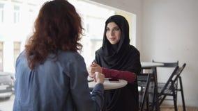 Διεθνής συνάντηση φίλων Μιλούν στον καφέ: η νέα μουσουλμανική γυναίκα στο μαύρο hijab μιλά στο θηλυκό της απόθεμα βίντεο