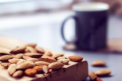 Διεσπαρμένα αμύγδαλα σε μια ξύλινες σανίδα και μια κούπα Στοκ φωτογραφίες με δικαίωμα ελεύθερης χρήσης