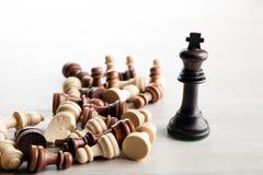 Διεσπαρμένα κομμάτια σκακιού και κομμάτι σκακιού του μαύρου βασιλιά σε μια GR Στοκ Εικόνες