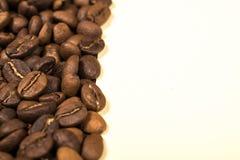 Διεσπαρμένα ψημένα φασόλια καφέ στο μπεζ υπόβαθρο στοκ φωτογραφία