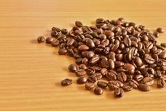 Διεσπαρμένα ψημένα φασόλια καφέ στο ξύλινο επιτραπέζιο υπόβαθρο στοκ εικόνα