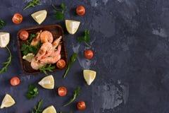 Διεσπαρμένες ντομάτες μαϊντανού, λεμονιών, rucola και κερασιών Στο κέντρο της αναταραχής στο τετραγωνικό πιάτο είναι γαρίδες σκοτ Στοκ φωτογραφία με δικαίωμα ελεύθερης χρήσης