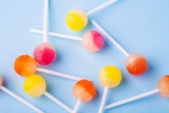Διεσπαρμένες lollipop καραμέλες στην μπλε τοπ άποψη υποβάθρου στοκ φωτογραφία