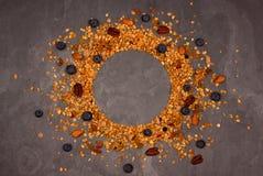 Διεσπαρμένο granola με τα καρύδια στο σκούρο γκρι υπόβαθρο στοκ εικόνες