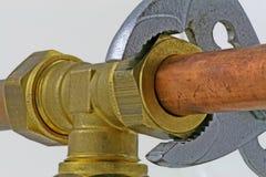 Διευθετήσιμο γαλλικό κλειδί υδραυλικών ` s που σφίγγει επάνω τις σωληνώσεις χαλκού Στοκ εικόνα με δικαίωμα ελεύθερης χρήσης