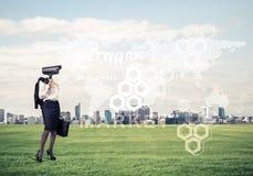 Διευθυνμένη κάμερα γυναίκα που στέκεται στην πράσινη χλόη ενάντια στα σύγχρονα citys Στοκ Εικόνες