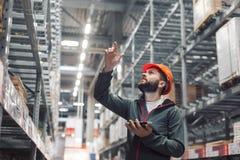 Διευθυντής αποθηκών εμπορευμάτων που ελέγχει τον κατάλογό του σε μια μεγάλη αποθήκη εμπορευμάτων Στοκ Εικόνες