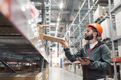 Διευθυντής αποθηκών εμπορευμάτων που ελέγχει τον κατάλογό του σε μια μεγάλη αποθήκη εμπορευμάτων Στοκ εικόνα με δικαίωμα ελεύθερης χρήσης