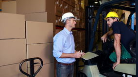 Διευθυντής αποθηκών εμπορευμάτων που συνεργάζεται με τον επιστάτη forklift απόθεμα βίντεο
