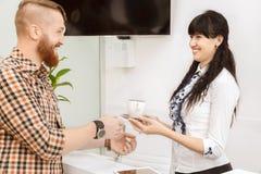 Διευθυντής γραφείων που προσφέρει στον πελάτη ένα φλυτζάνι του τσαγιού στοκ φωτογραφία με δικαίωμα ελεύθερης χρήσης