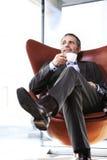 Διευθυντής γραφείων στην κόκκινη έδρα που απολαμβάνει τον καφέ. Στοκ Φωτογραφία