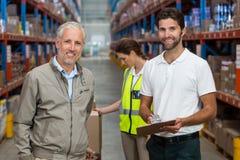 Διευθυντής και άνδρες εργαζόμενος αποθηκών εμπορευμάτων που χαμογελούν εργαζόμενος Στοκ φωτογραφία με δικαίωμα ελεύθερης χρήσης