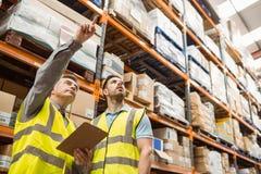 Διευθυντής και επιστάτης αποθηκών εμπορευμάτων που εργάζονται από κοινού Στοκ εικόνα με δικαίωμα ελεύθερης χρήσης