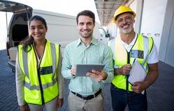 Διευθυντής και εργαζόμενοι αποθηκών εμπορευμάτων που στέκονται με την ψηφιακές ταμπλέτα και την περιοχή αποκομμάτων στοκ εικόνα