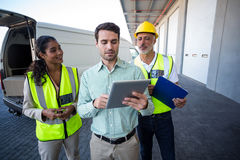Διευθυντής και εργαζόμενοι αποθηκών εμπορευμάτων που συζητούν με την ψηφιακή ταμπλέτα στοκ εικόνα