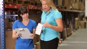 Διευθυντής και εργαζόμενος που ελέγχουν τα αγαθά στην αποθήκη εμπορευμάτων απόθεμα βίντεο