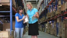 Διευθυντής και εργαζόμενος που ελέγχουν τα αγαθά στην αποθήκη εμπορευμάτων φιλμ μικρού μήκους