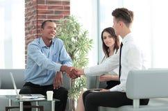 Διευθυντής και πελάτης χειραψιών σε ένα σύγχρονο γραφείο στοκ εικόνες