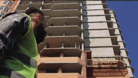 Διευθυντής κατασκευής σε ένα κράνος με μια γενειάδα και mustache στο υπόβαθρο μιας πολυκατοικίας 4K απόθεμα βίντεο