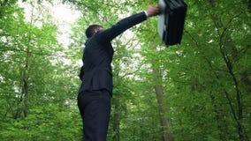 Διευθυντής με τα όπλα διάδοσης χαρτοφυλάκων και αίσθημα της ενέργειας της φύσης στο πράσινο πάρκο φιλμ μικρού μήκους