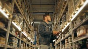 Διευθυντής με το PC ταμπλετών που ελέγχει τα αγαθά στην αποθήκη εμπορευμάτων υπεραγορών απόθεμα βίντεο