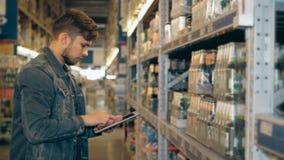 Διευθυντής με το PC ταμπλετών που ελέγχει τα αγαθά στην αποθήκη εμπορευμάτων υπεραγορών φιλμ μικρού μήκους