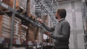 Διευθυντής με το PC ταμπλετών που ελέγχει τα αγαθά στην αποθήκη εμπορευμάτων υπεραγορών Σύγχρονο απόθεμα επίπλων απόθεμα βίντεο