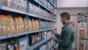 Διευθυντής με το PC ταμπλετών που ελέγχει τα αγαθά στο κατάστημα αποθηκών εμπορευμάτων υπεραγορών αυτοκινήτων απόθεμα βίντεο