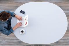 Διευθυντής που εργάζεται στον υπολογιστή στον γκρίζο πίνακα Στοκ Φωτογραφία