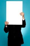 Διευθυντής που κρύβει το πρόσωπό του πίσω από την άσπρη αγγελία εμβλημάτων Στοκ εικόνες με δικαίωμα ελεύθερης χρήσης