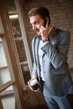 Διευθυντής που μιλά στο τηλέφωνο κυττάρων στην εταιρία στοκ φωτογραφίες
