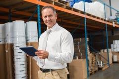 Διευθυντής που χρησιμοποιεί την ψηφιακή ταμπλέτα στην αποθήκη εμπορευμάτων στοκ φωτογραφία